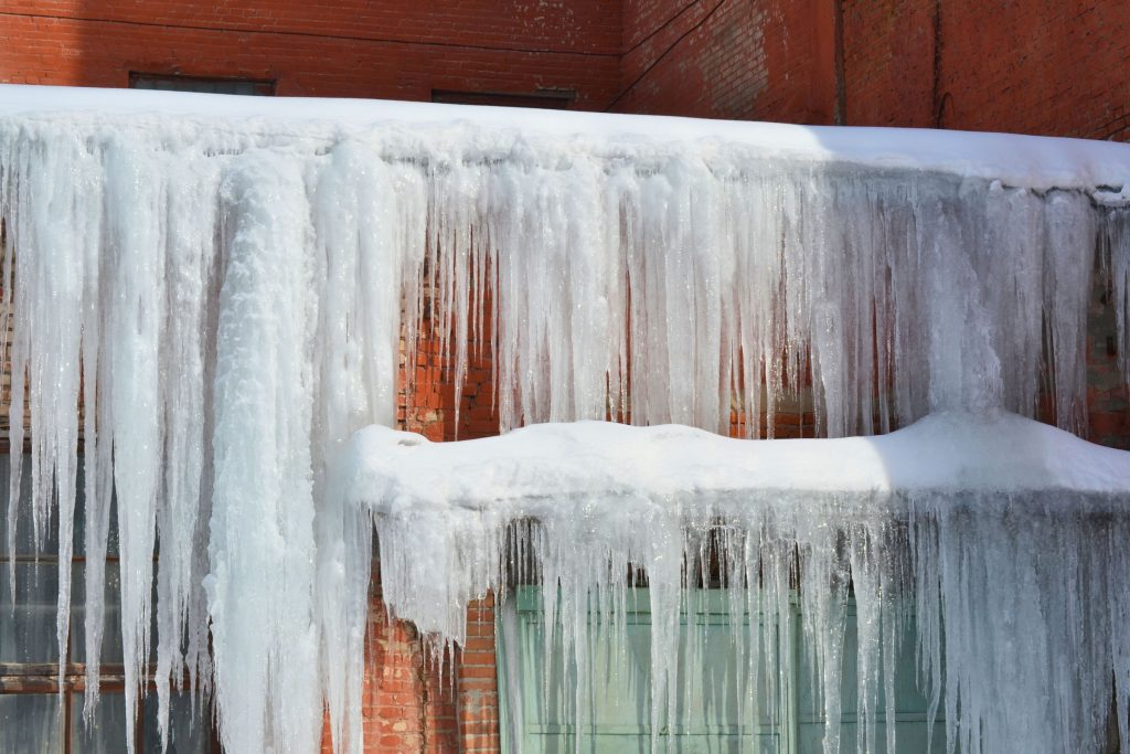 A home with severe ice dams and gigantic icicles hanging from the roof.